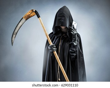 Grim Reaper making a phone call. Photo of silhouette grim reaper with smartphone. Death