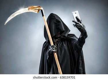 Grim Reaper making selfie photo on smartphone. Photo of personification of death wielding a large scythe in silhouette.