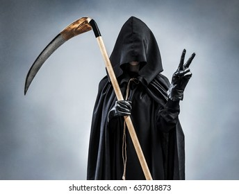 Grim Reaper showing Victory sign. Photo of silhouette grim reaper showing victory gesture or two finger. Death