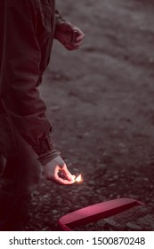 a grim Sepia Photo of a guy in a jacket and jeans in a Park in nature kindling a fire in the evening at dusk in force industrial Apocalypse
