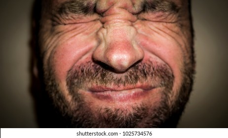 grimace of pain on the face of an adult male