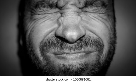 grimace of pain on the face of an adult male. black and white photo