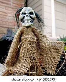 Grimacing Halloween ghoul decoration in shrouded burlap.