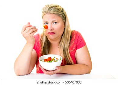 Grimacing overweight woman with bowl of healthy salad on white