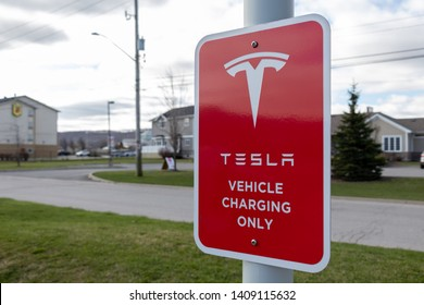 "GRIMSBY, CANADA- April 24, 2019: Tesla ""Electric Vehicle Only"" Sign at Tesla Supercharger Station."