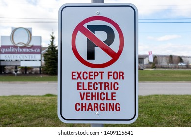 "GRIMSBY, CANADA - April 24, 2019: ""No Parking Except For Electric Vehicle Charging"" sign at Tesla Supercharger Station."
