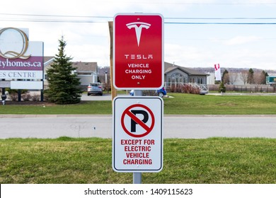 "GRIMSBY, CANADA - April 24th, 2019: ""Tesla Vehicle Charging Only"" and ""No Parking Except For Electric Vehicle Charging"" sign at Tesla Supercharger Station."