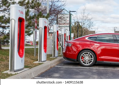 GRIMSBY, CANADA - April 24th, 2019: Tesla Supercharger Station with Tesla Model S, parked and charging in Grimsby, Ontario.