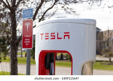 "GRIMSBY, CANADA - April 24th, 2019: Top of Tesla Supercharger Stall with ""Tesla Vehicle Charging Only"" sign in the backgroudn."