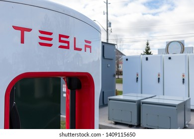 GRIMSBY, CANADA - April 24th, 2019: Tesla Supercharger in-front of Tesla power technology for Supercharger Station.