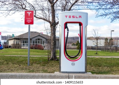 "GRIMSBY, CANADA - April 24th, 2019: Tesla Supercharger Stall beside ""Tesla Vehicle Charging Only"" sign in Grimsby, Ontario."