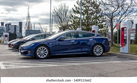 GRIMSBY, CANADA - April 24th, 2019: Blue Tesla Model S, Red Tesla Model S and Red Tesla Model 3 plugged-in, supercharging at Tesla's Grimsby location.