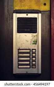 A grimy apartment intercom in New York City.