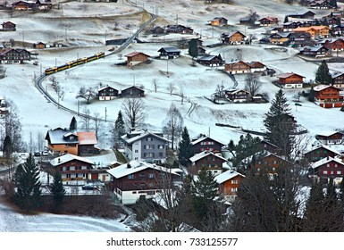 "GRINDELWALD, SWITZERLAND- December 16, 2016. Grindelwald village, in the ""shadow"" of Mount Eiger, in the Alps. You can also see the train that goes to Jungfraujoch, Europe's highest railway station."