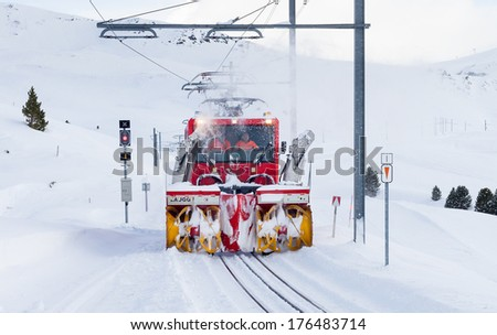 GRINDELWALD, SWITZERLAND - FEBRUARY 3, 2014 : A locomotive with snow blower attachments clears snow from the Lauterbrunnen to ??Kleine Scheidegg railway high in the Bernese Alps in Switzerland.