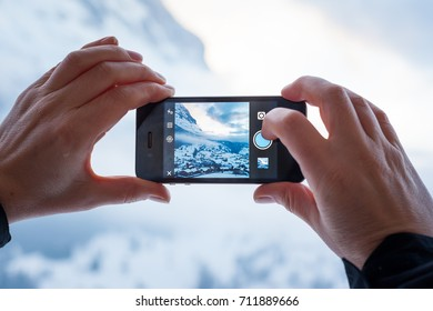 GRINDELWALD, SWITZERLAND - FEBRUARY 4, 2014: Woman taking a photograph of mountains using the Instagram App on an Apple iPhone. Instagram allows users to easily share their mobile photographs online.