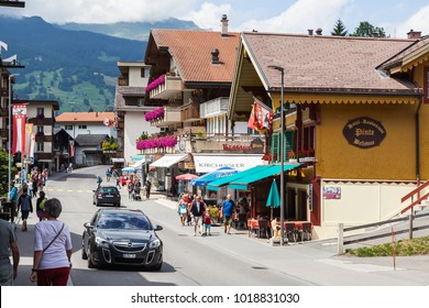 Grindelwald, Switzerland - JULY 23rd, 2017: Alpine village and its traditional architecture is seen between the street and the wooded areas which are on the slopes of the mountains.