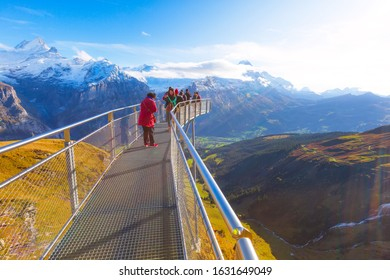 Grindelwald, Switzerland - October 10, 2019: People taking photos on sky cliff walk metal bridge at First peak of Swiss Alps mountain, snow peaks panorama, jungfrau, Europe
