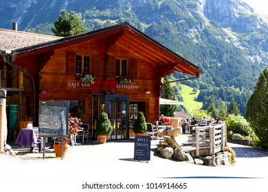 Grindelwald, Switzerland - September 21, 2017: The traditional wooden building houses a restaurant, which is located near the slope of a large mountain. There is also an outdoor restaurant there