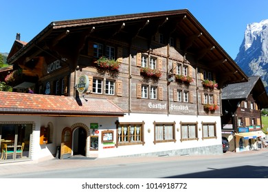 Grindelwald, Switzerland - September 21, 2017: The guest house. On the wooden facade, beautiful windows are decorated with flowers and in addition wooden shutters has been installed there.