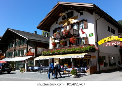 Grindelwald, Switzerland - September 21, 2017: The Alpine architecture decorated with flowers and beautiful windows equipped with shutters create the atmosphere of this town, which is a famous resort.