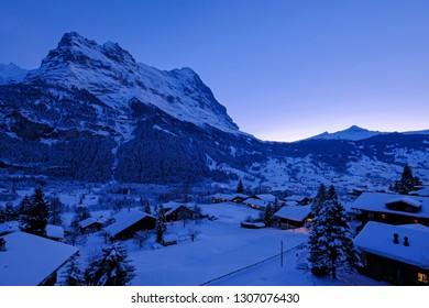 Grindelwald village at dusk with Mt. Eiger peak in the background, snow covered landscape in winter, Grindelwald, Bern, Switzerland, Europe