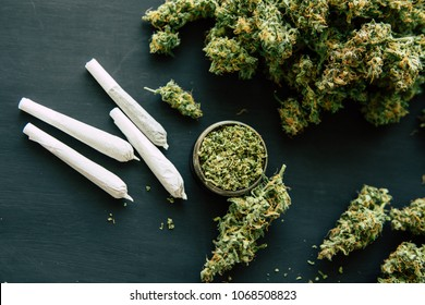 Grinder with crushed cannabis flowers and Joint and weed on the background of a black wooden table top view close up