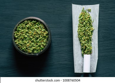 Grinder with crushed cannabis flowers and not twirled jamb on the background of a black wooden table