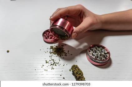 Grinder in woman hand. Medical marijuana buds in crasher. Cannabin on white table (background)