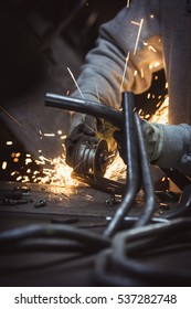 Grinding loops of steel pipe with many sparks on a work table