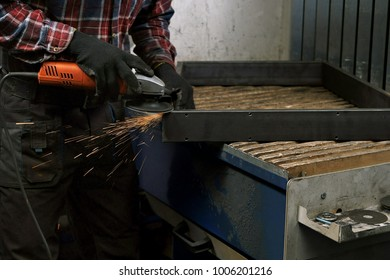 Grinding, man grinding metal, sparks flying from under the grinding wheel.