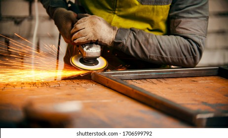 Grinding the seams of an iron frame - bright sparkles comes off the metal in the process