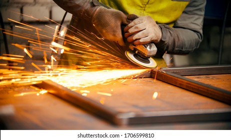 Grinding the seams of a metal frame - bright sparkles comes off the metal