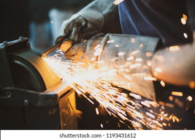 Grinding steel with lot of sparks by worker in factory