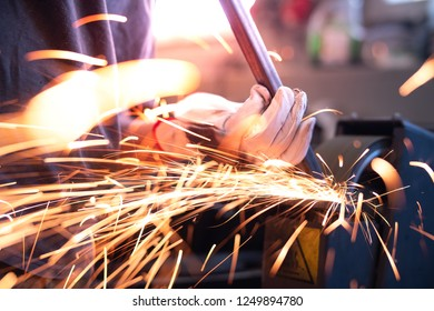Grinding tube square steel with lot of sparks.