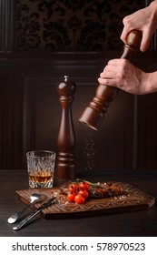Grindling pepper on the rosemary ribeye steak, close-up. Flatware, wooden serving board and a glass of whiskey. Adding spices.