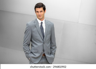 Grinning businessman in a trendy suit young and positive expression at the office modern corporate leader