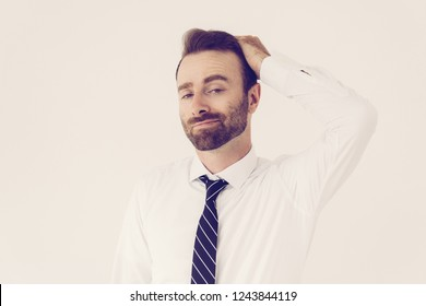 Grinning conceited businessman self satisfied. Young man in tie and white shirt touching hair with vain face. Vanity and ambition concept
