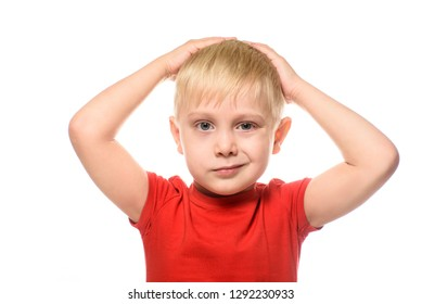 Grinning, fair-haired boy in a red t-shirt folded his arms behind his head. Isolate on white background