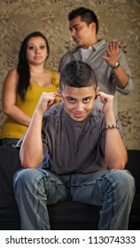 Grinning Hispanic teenager plugging his ears with frustrated parents