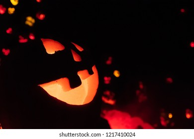 Grinning jack-o-lantern in foreground of holiday decorations