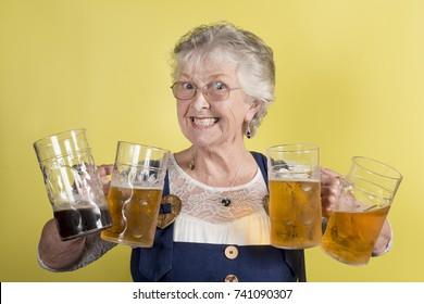 Grinning old lady holding four big crystal mugs filled with beer on yellow background