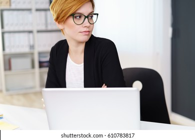 Grinning young single woman in short red hair sitting in office looking over shoulder. Laptop in front of her.