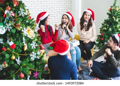 Griop of Asians are party songs and exchange gifts to celebrate Christmas together playfully.