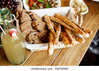 Grissini bread sticks with roasted sesame seeds and slices of bread in a basket in an italian restaurant