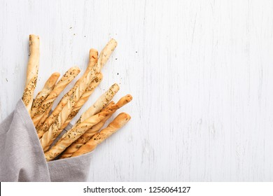 Grissini on the white wooden table with napkin. Traditional italian snack with herbs. Top view.