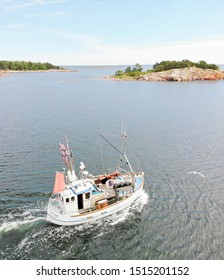 GRISSLEHAMN, SWEDEN - JUL 03, 2019: Small fishingboat on the sea on the way to put the fishing nets in the water, islets and horizon in the background. July 03, 2019 in Grisslehamn