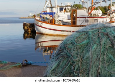 GRISSLEHAMN, SWEDEN - JUL 08, 2017: Fishing net in the foreground and an unsharp taditional fishing boat in the background. Grisslehamn Sweden, July 08, 2017