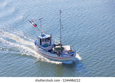 GRISSLEHAMN, SWEDEN - JUL 13, 2018: Small fishing boat on the blue sea heading back after taking up the net used to catch cod on the Baltic sea in Scandinavia. July 13, 2018