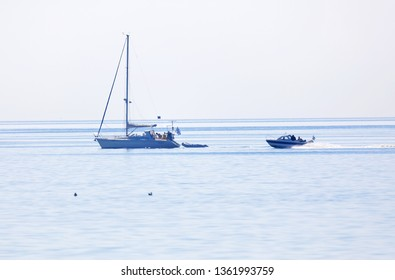 GRISSLEHAMN, SWEDEN - JUL 15, 2018: One sailship and one motor boat on the blue ocean in the swedish archipelago, islets in the background. July 15 2018, Grisslehamn, Sweden